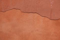 Old terracotta painted stucco wall with cracked plaster. Backgro Royalty Free Stock Photography