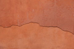 Old terracotta painted stucco wall with cracked plaster. Backgro Stock Image