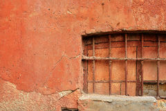 Old terracotta plastered wall of red brick with closed window. Stock Photography
