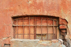 Old terracotta plastered wall of red brick with closed window. Royalty Free Stock Images
