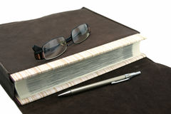 Old text book or bible with pen and eyeglasses and leather bag Stock Photography
