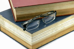 Old text books or bible with eyeglasses. On them stock image