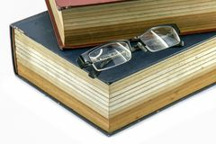 Old text books or bible with eyeglasses on them. Few Old text books or bible with eyeglasses on them royalty free stock photography