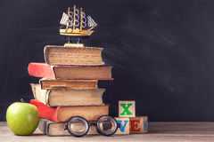 Old textbooks are on the rustic wooden table on a background of black chalk board. Stock Photos