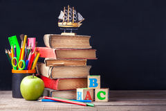 Old textbooks and school supplies are on the rustic wooden table on a background of black chalk board. Stock Images