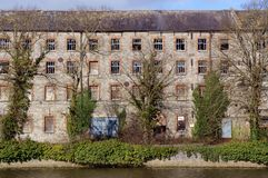 Old Textile Mill. The wall and broken and boarded windows of an old textile mill on the bank of the River Boyne in Drogheda, Ireland. The building is partly Royalty Free Stock Photo
