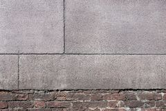 Old texture of a brick wall with grained cement plaster Royalty Free Stock Photo