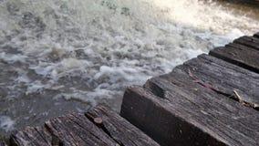 Old texture wooden bridge over strong stream Stock Photos