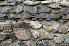Old textured gray background of a wall of stone and cement. Stock Photos