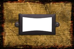 An old textured metal frame on wood background. An old textured metal frame with screws on a grunge background. Insert your own text or image royalty free stock image