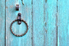 Old textured turquoise wooden door with aged metal door handle in the form of ring. Stock Photography