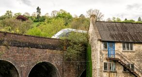 Old 18th Century mill buildings and modern Inter-City train, Brimscombe Port, Stroud, The Cotswolds stock image