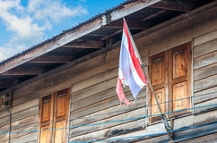 Old Thai flag with Thai house in rural Stock Photo
