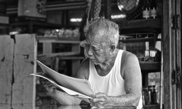 Old thai man reading newspaper stock images