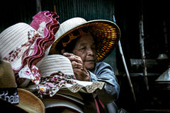 Old Thai woman Selling hats at Damnoen Saduak Floating Market. Stock Image