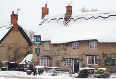 Old thatched public house in the snow. Stock Photography