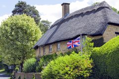 Flying Union Jack in a garden of country house in an english countryside. Old thatched roof golden stone cottage by a rural village road, with waving British Royalty Free Stock Image