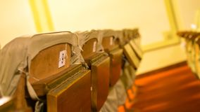 Old theater chairs with number and small table stock photos