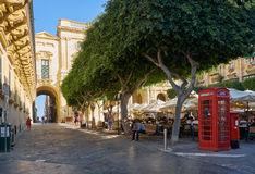 Old Theatre Street, Valletta, Malta. VALLETTA, MALTA - JULY 24, 2015: The view of the Old Theatre Street with the outdoor cafe full of people in the summer day Royalty Free Stock Photo