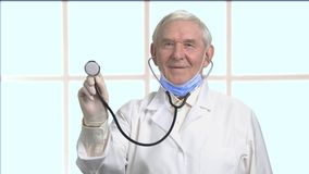 Old therapist in white coat checking your heartbeat. Doctor using stethoscope, front view. Bright checkered window background stock footage