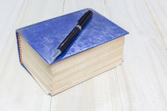 Old thick book blue cover and pen on wooden background Stock Photos