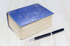 Old thick book blue cover and pen on wooden background Stock Image