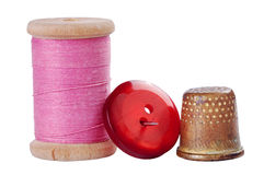 Old thimble, button and needle with pink thread. On white with shadow Royalty Free Stock Photo