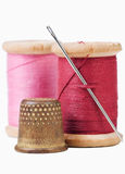 Old thimble and needle with pink and red thread Stock Photo