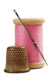 Old thimble and needle with pink thread. On white with shadow Royalty Free Stock Images