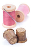 Old thimbles and needle with pink thread. On white with shadow Royalty Free Stock Images