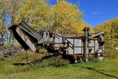 Old threshing machine in the autumn turning leaves Royalty Free Stock Photo
