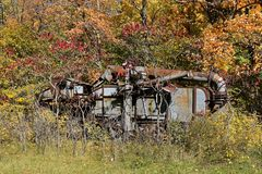 Old threshing machine in the autumn leaves Royalty Free Stock Photos