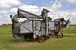 An old threshing machine resides in a field with a freight train passing in the background Royalty Free Stock Image