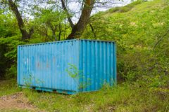 The old thrown iron blue container Stock Photos