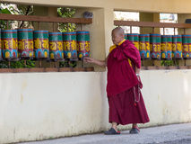 Old Tibetan Buddhist monk turning the prayer wheels at temple in the Dharamsala, India Stock Photo