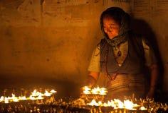 Old tibetan woman. Putting incense butter candles outside the Boudhanath Stupa in Kathmandu, Nepal Royalty Free Stock Image