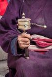 Old Tibetan woman holding buddhist prayer wheel in Lamayuru Gompa, , Ladakh, India. Royalty Free Stock Image