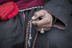Old Tibetan woman holding buddhist rosary in Hemis monastery, Ladakh, India. Stock Photos