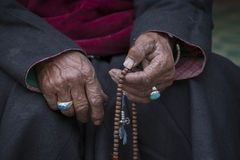 Old Tibetan woman holding buddhist rosary in Hemis monastery, Ladakh, India. Stock Photography