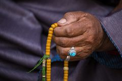 Old Tibetan woman holding buddhist rosary in Hemis monastery, Ladakh, India. Hand and rosary, close up stock photo