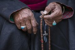 Old Tibetan woman holding buddhist rosary in Hemis monastery, Ladakh, India. Hand and rosary, close up. Old hands of a Tibetan woman holding prayer buddhist Stock Images