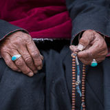 Old Tibetan woman holding buddhist rosary, Ladakh, India. Hand and rosary. Old Tibetan woman holding buddhist rosary in Hemis monastery, Ladakh, India. Hand and Royalty Free Stock Images