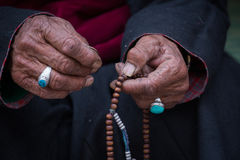 Old Tibetan woman holding buddhist rosary, Ladakh, India. Hand and rosary. Old Tibetan woman holding buddhist rosary in Hemis monastery, Ladakh, India. Hand and Royalty Free Stock Photography