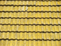 Old tile roof. Old yellow tile on a roof of the small house Stock Image