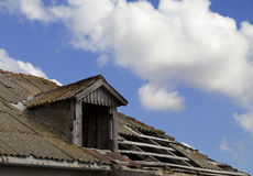 Old tile roof with holes and blue sky with clouds. In sun day Stock Image