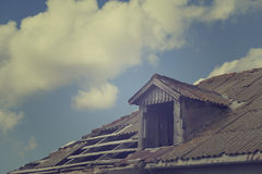 Old tile roof with holes and sky with clouds Royalty Free Stock Image