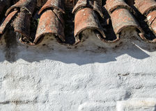 Old tile roofing and stucco wall. Vintage Spanish architecture, roof tiles and adobe wall Royalty Free Stock Image