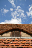 Old tiled roof with attick window Stock Photo