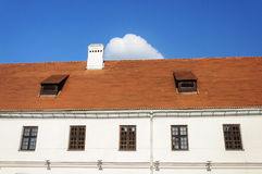 Old tiled roof with two attic windows and chimney Stock Image