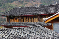 Old tiled roofs and frying corn. In Yunnan, China Stock Image